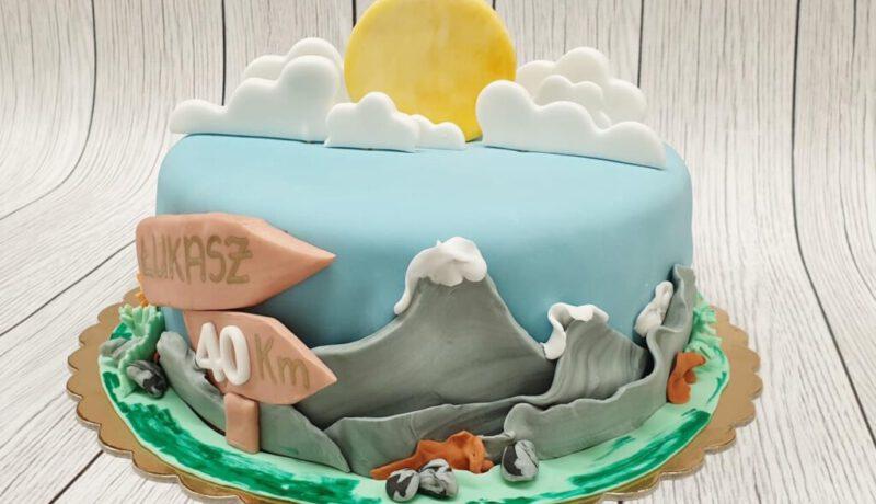 Tort z górskim pejzażem, niebem i słońcem