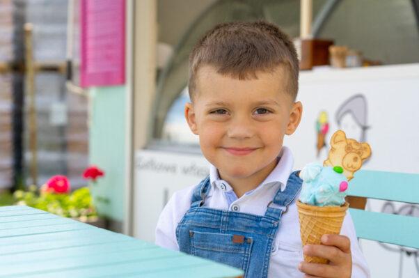 Dziecko z porcją lodów w dłoni, w tle stoisko Cukierni JoAsia
